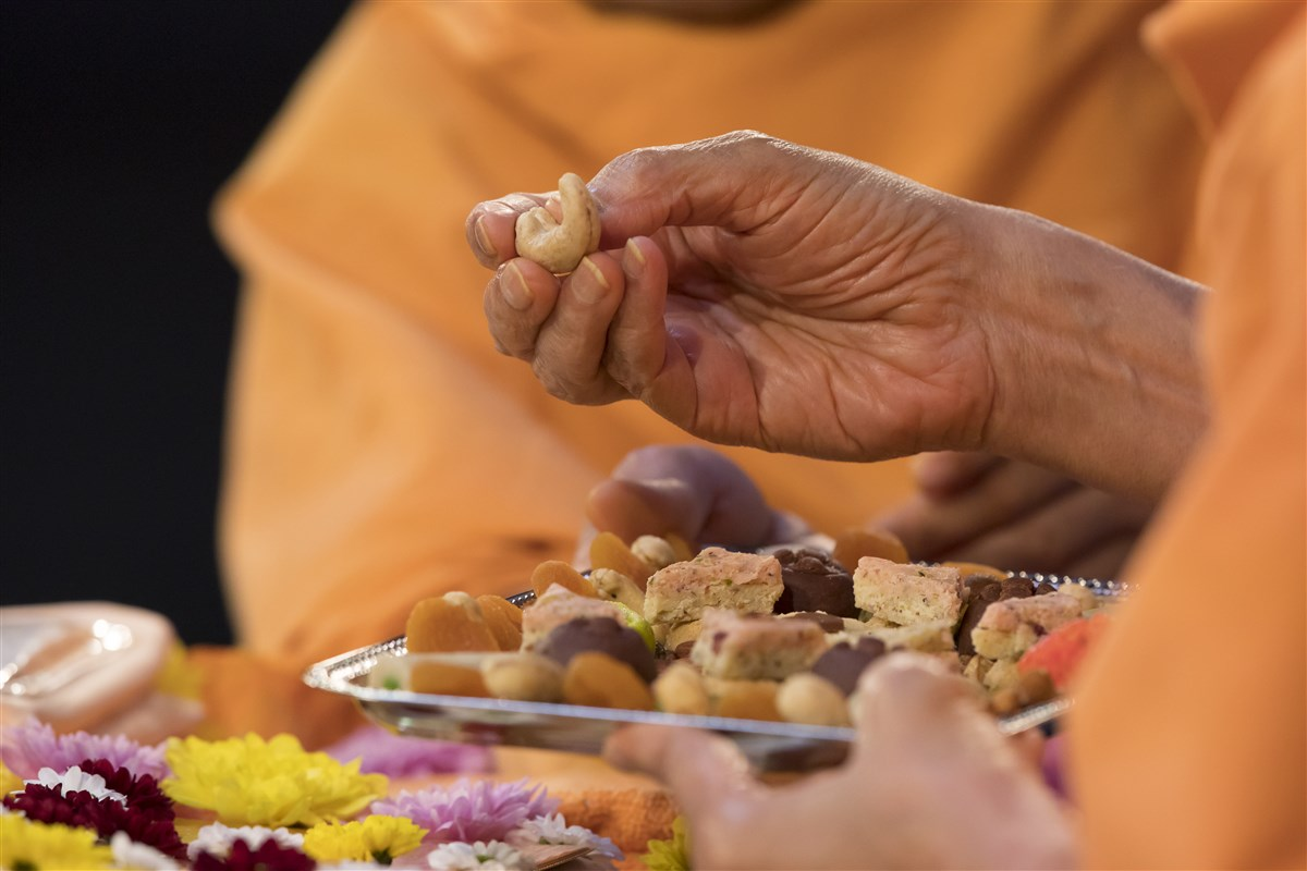 Swamishri offers a cashew from the thal to the murtis