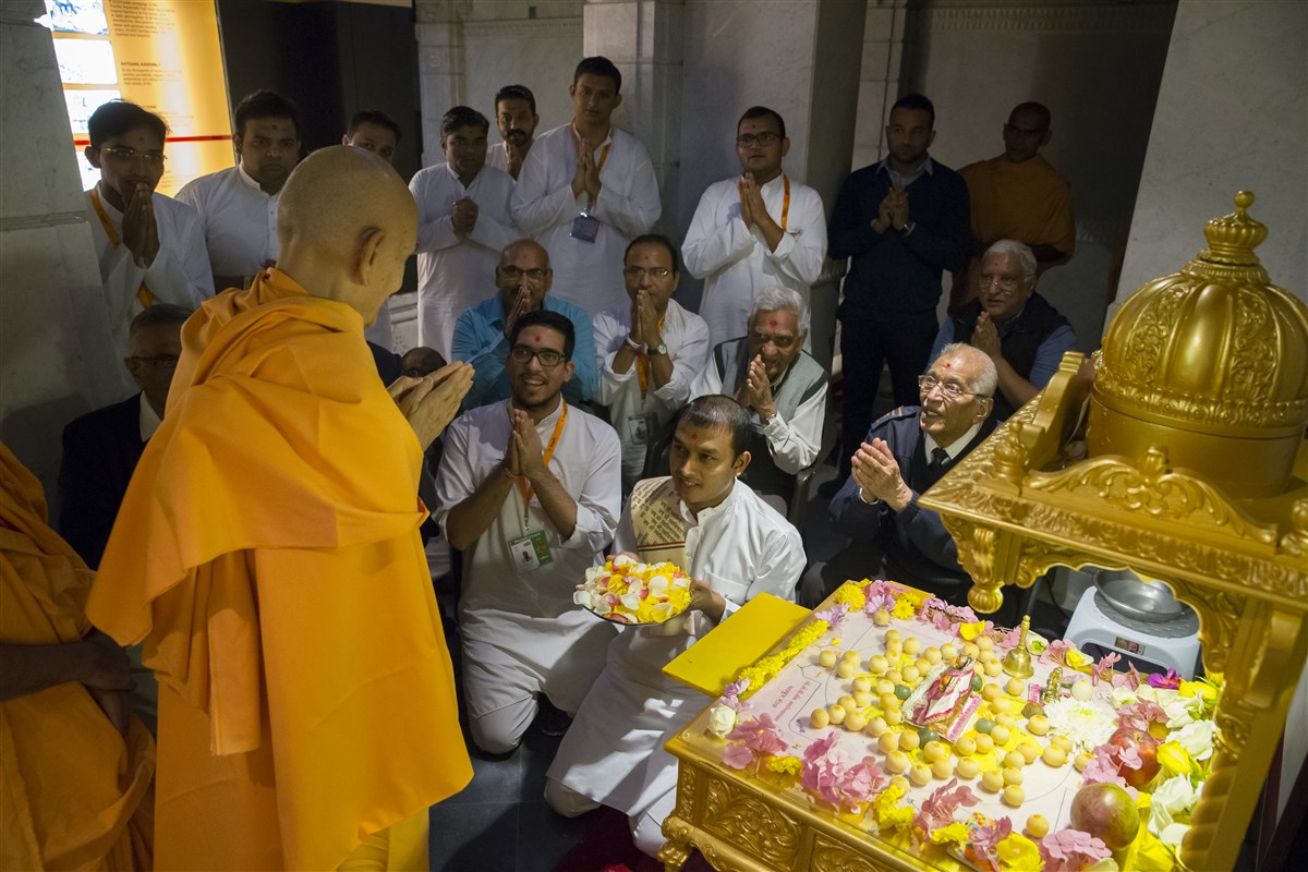 Swamishri greets devotees with folded hands performing the mahapuja