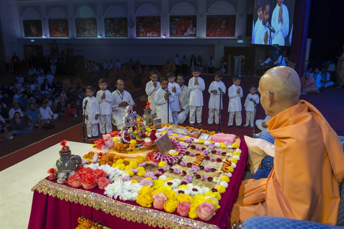 Children present various scriptural passages before Swamishri in his puja
