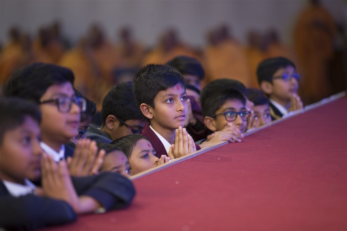 Children greet Swamishri with folded hands