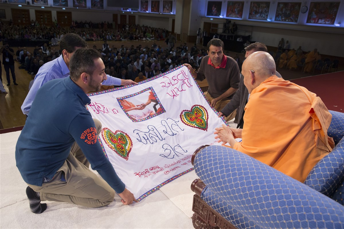 Lead volunteers of the Sanyukta Mandal honour Swamishri with a decorative shawl