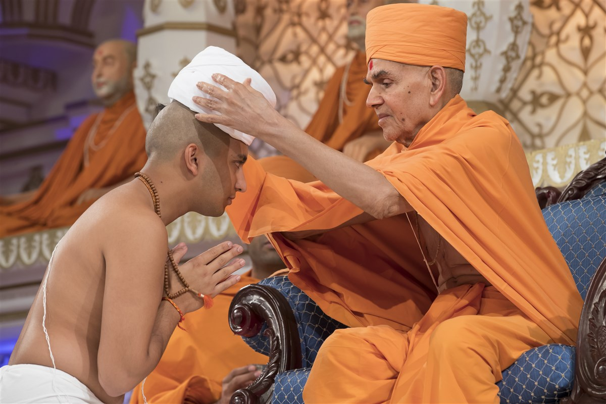 Swamishri places a new pagh upon the new ordinand