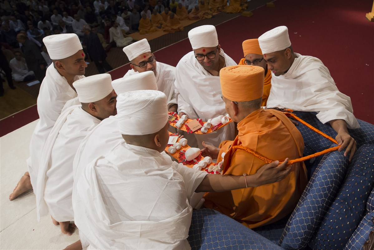 The newly ordained honour Swamishri with a thematic garland
