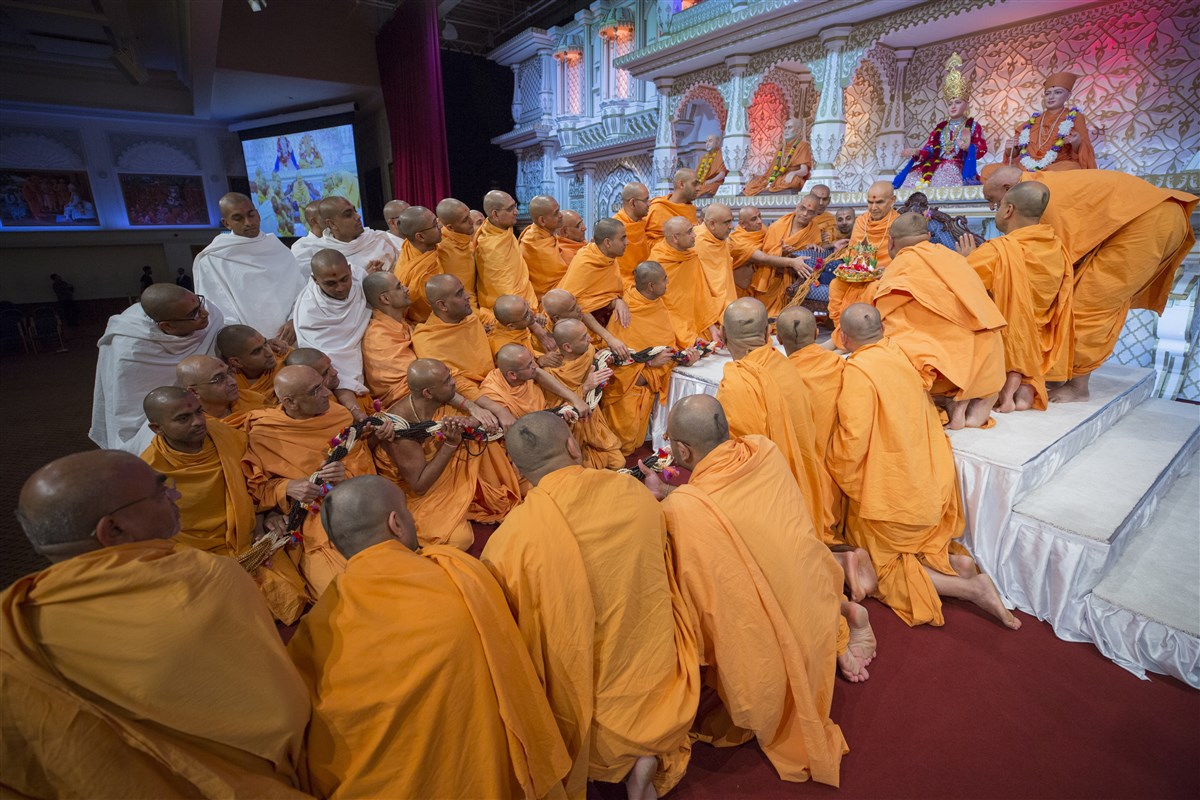 Swamis and parshads honour Shri Harikrishna Maharaj and Swamishri with a grand garland of rosaries