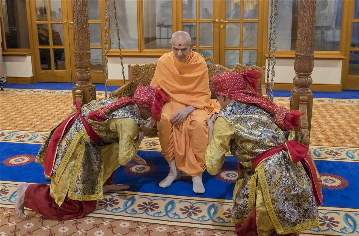 ... before two dancers call upon Swamishri to join the evening assembly
