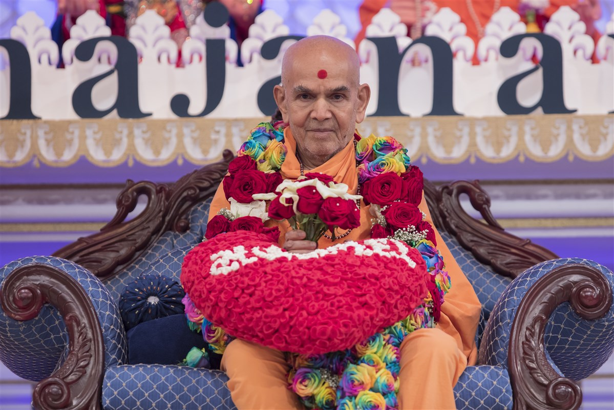 Swamishri is honoured with a colourful garland of fresh flowers, a bouquet and heart-shaped pillow