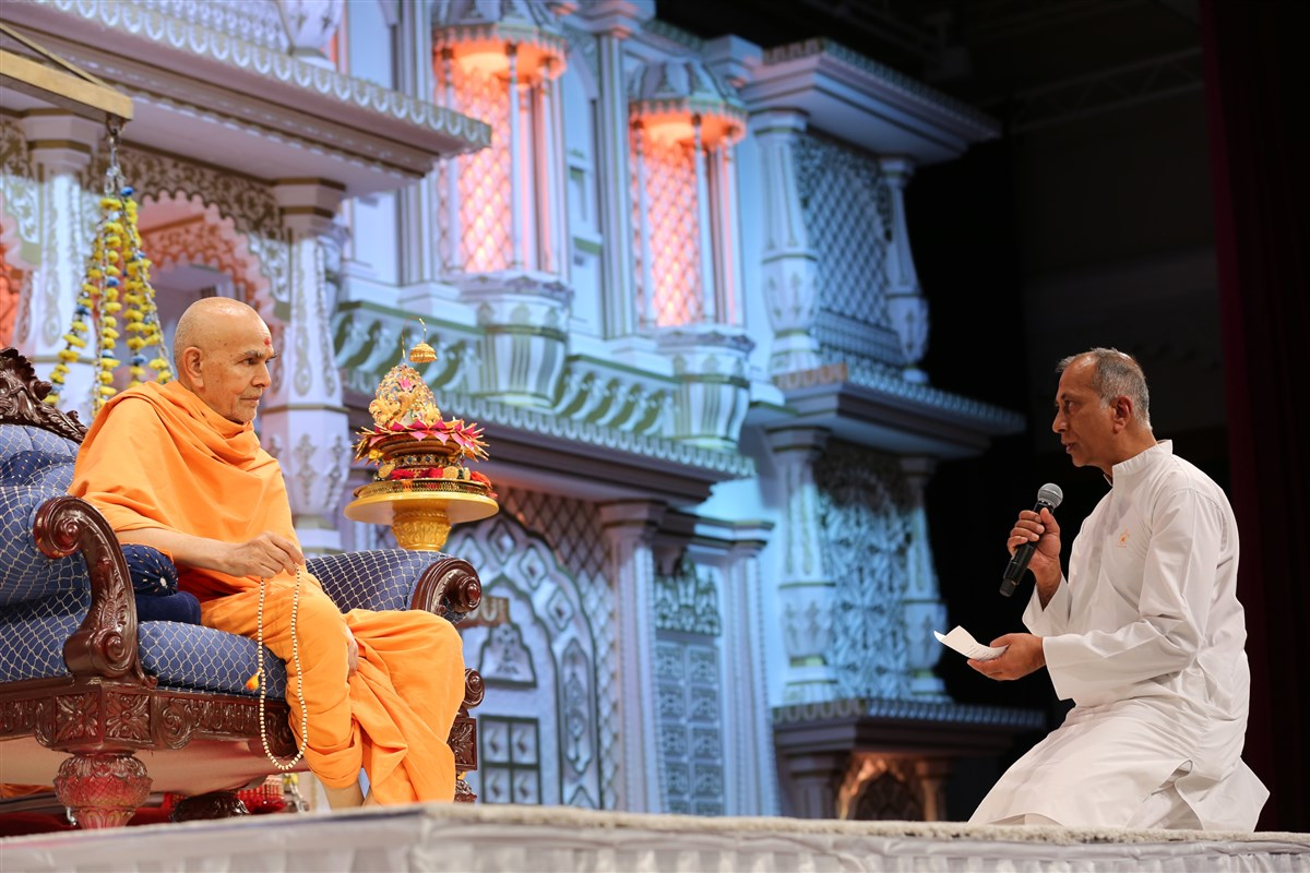 A senior devotee prays before Swamishri