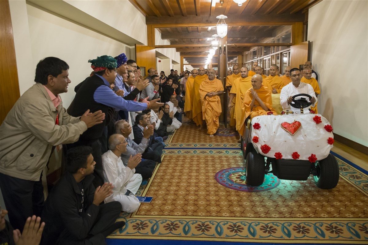 Devotees present short verses as Swamishri passes on his way to the assembly hall