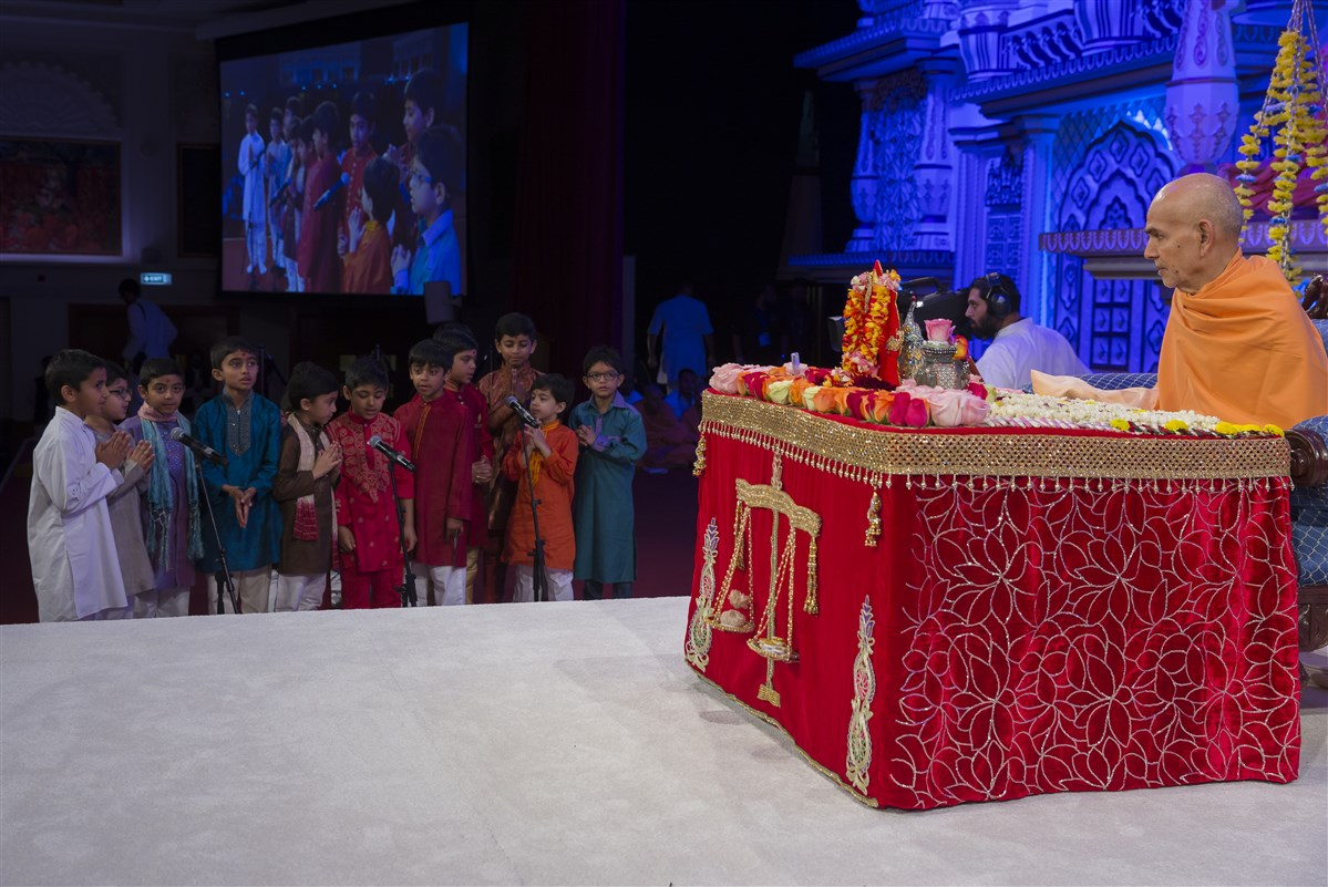 Children present scriptural passages in Swamishri's puja