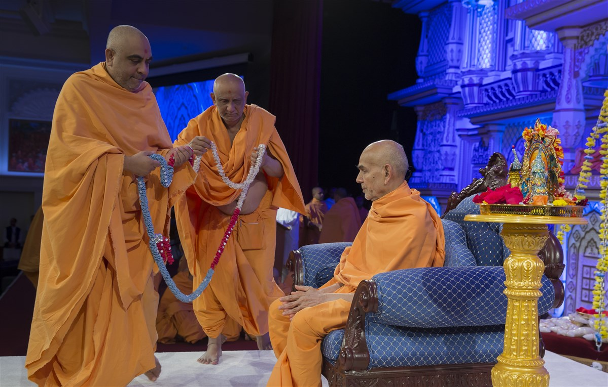 Atmaswarupdas Swami and Yogvivekdas Swami honour Swamishri with a garland