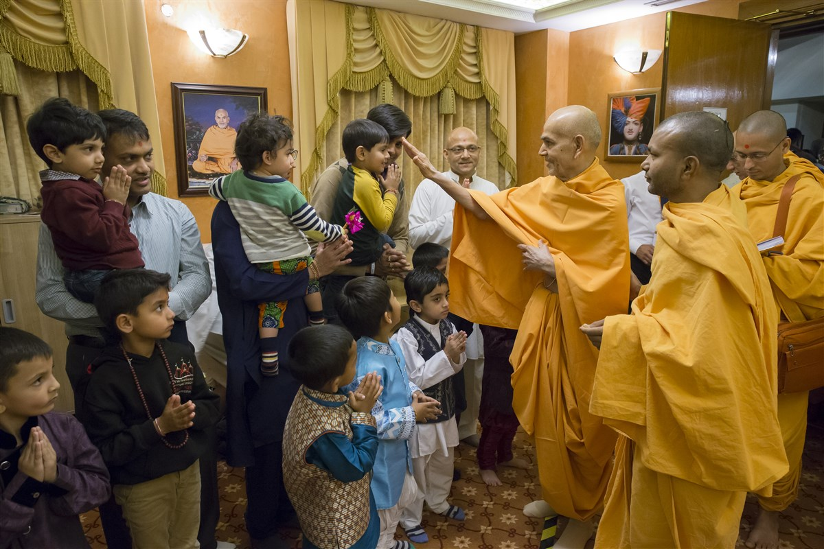 Swamishri continues to bless children in a meeting room