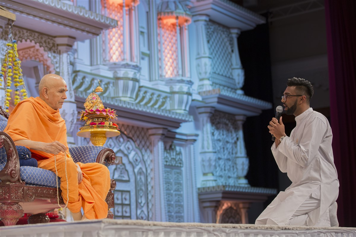 A young adult prays before Swamishri