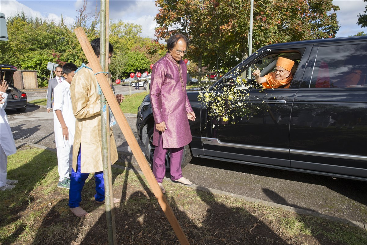 As he departs, Swamishri scatters flower petals to bless the commencement of the mandir's new landscaping