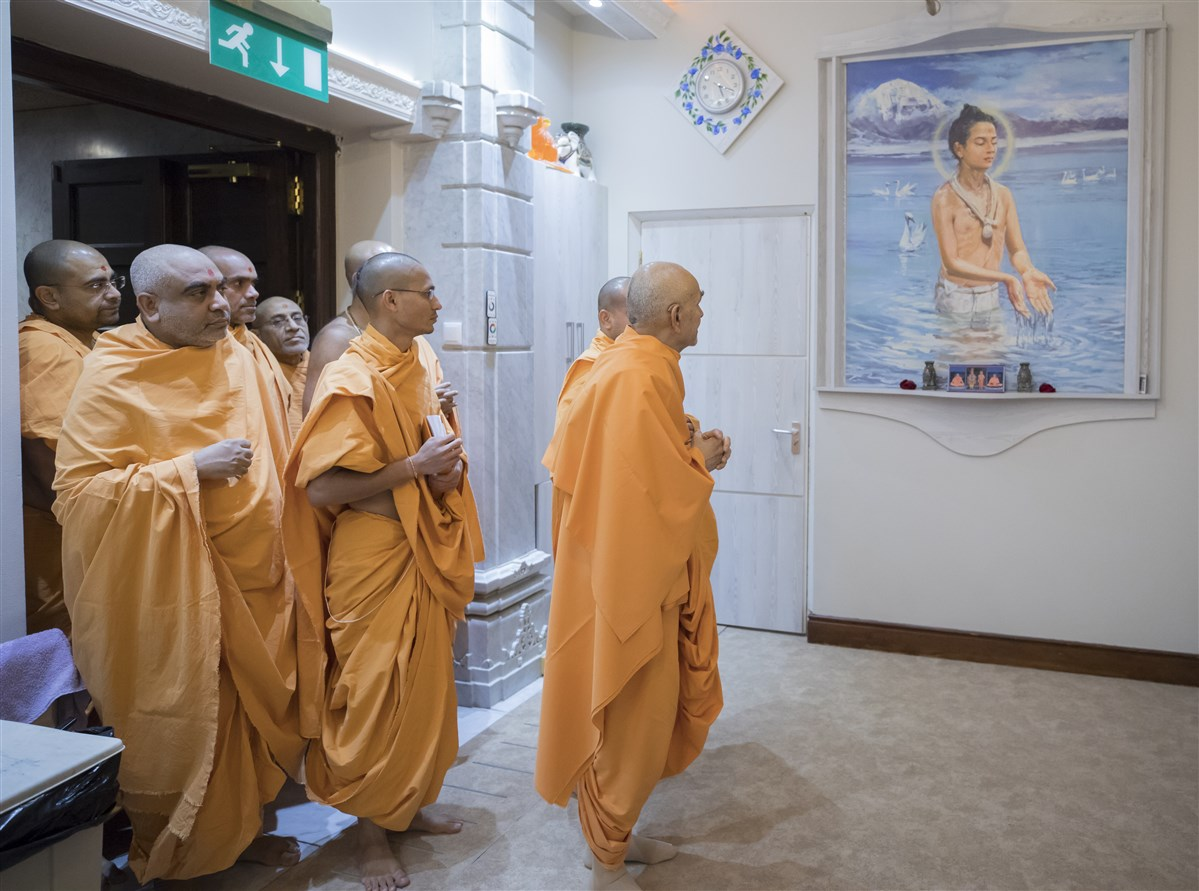 Param Pujya Mahant Swami Maharaj observes a painting of Nilkanth Varni on his way to the Abhishek Mandap