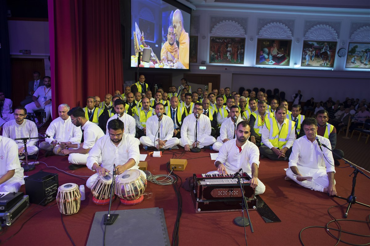 Youths and volunteers sing in Swamishri's puja