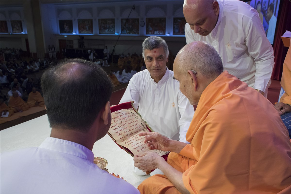 Swamishri reads a prayer presented by the female devotees of Luton Mandir