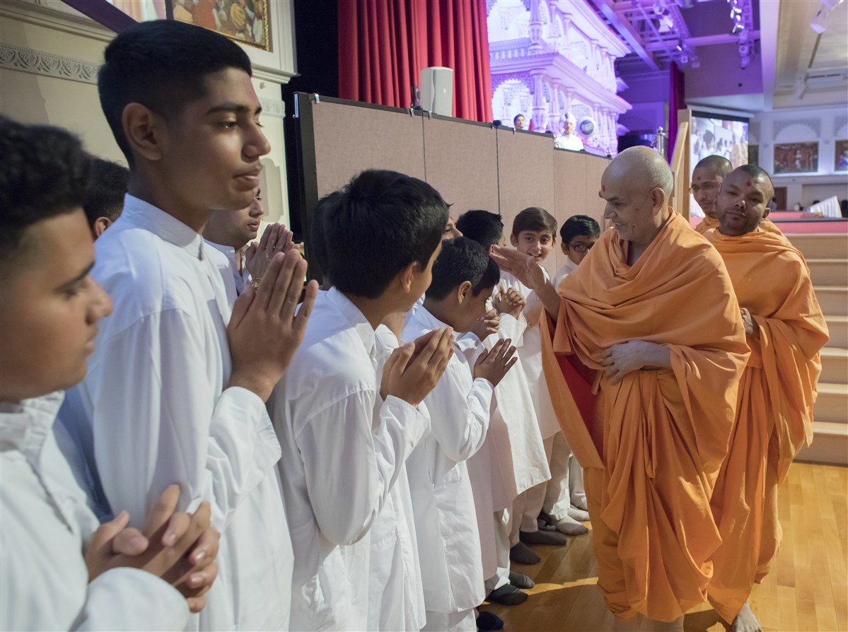 Swamishri blesses children as he departs the hall