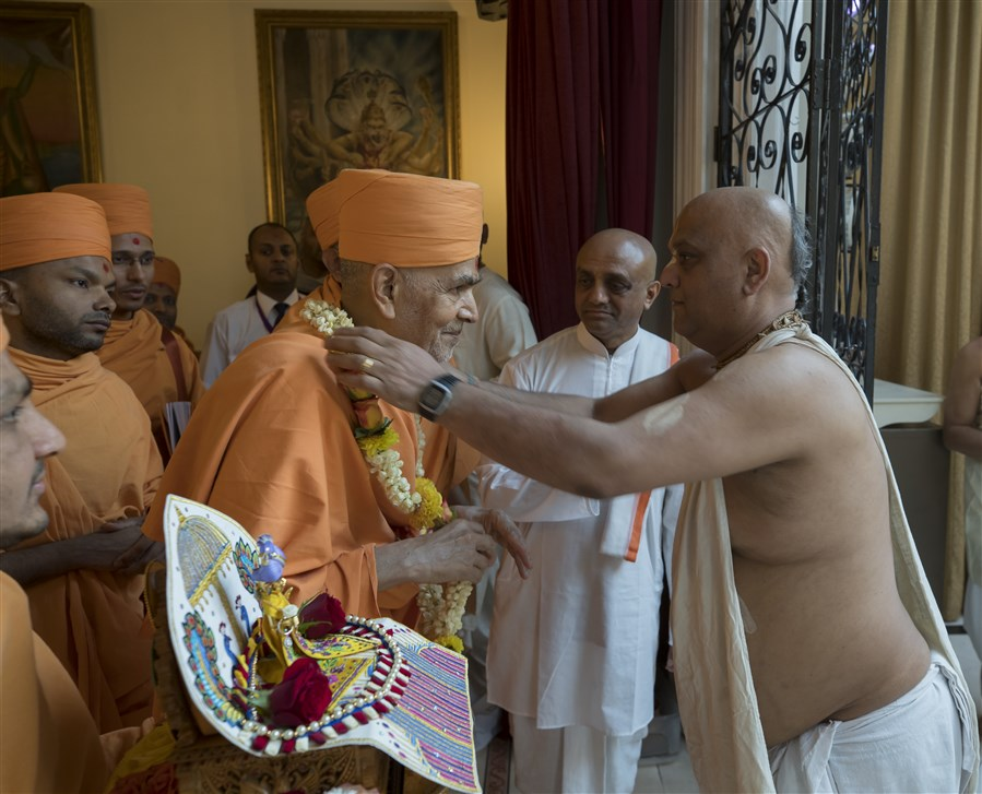 The temple pujari honours Swamishri with a flower garland