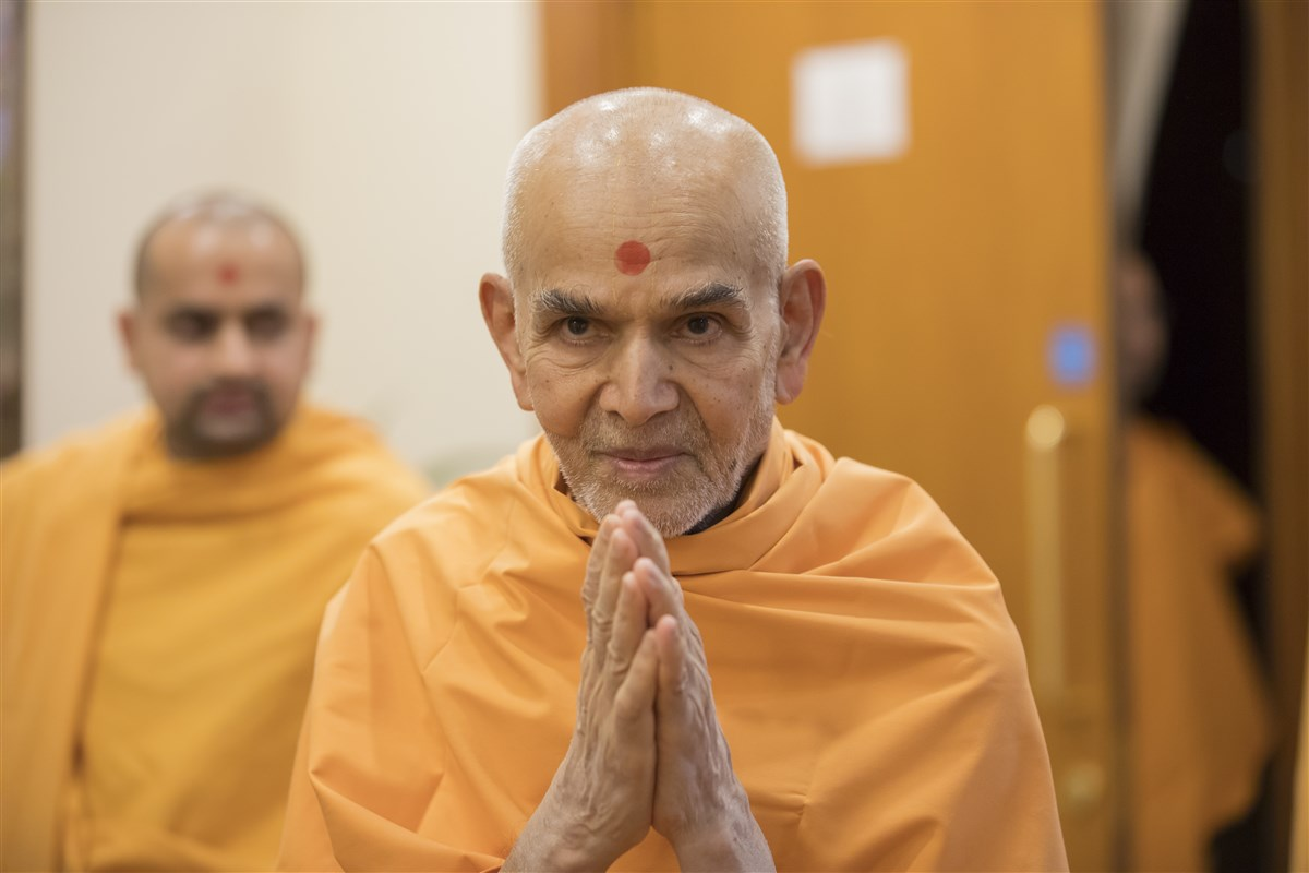 Param Pujya Mahant Swami Maharaj exits his room with folded hands...