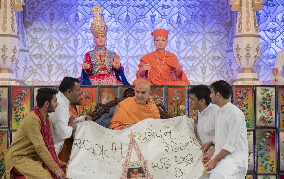 Volunteers from Europe offer Swamishri a decorative shawl
