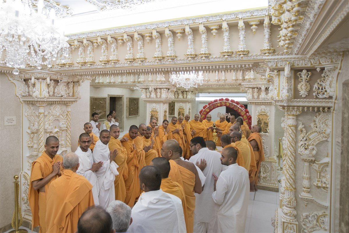 Swamishri greets the swamis and parshads as they collectively perform the abhishek of Shri Nilkanth Varni