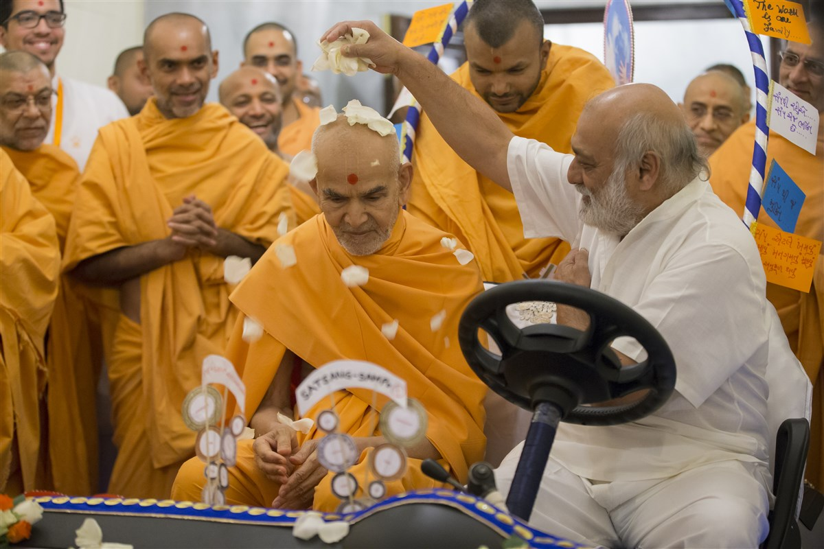 Swamishri is honoured with flower petals by an old volunteer who had served as Pramukh Swami Maharaj's driver for several years