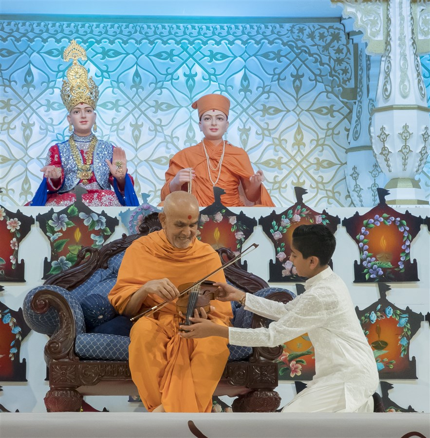 ... who presents his violin to Swamishri to be sanctified