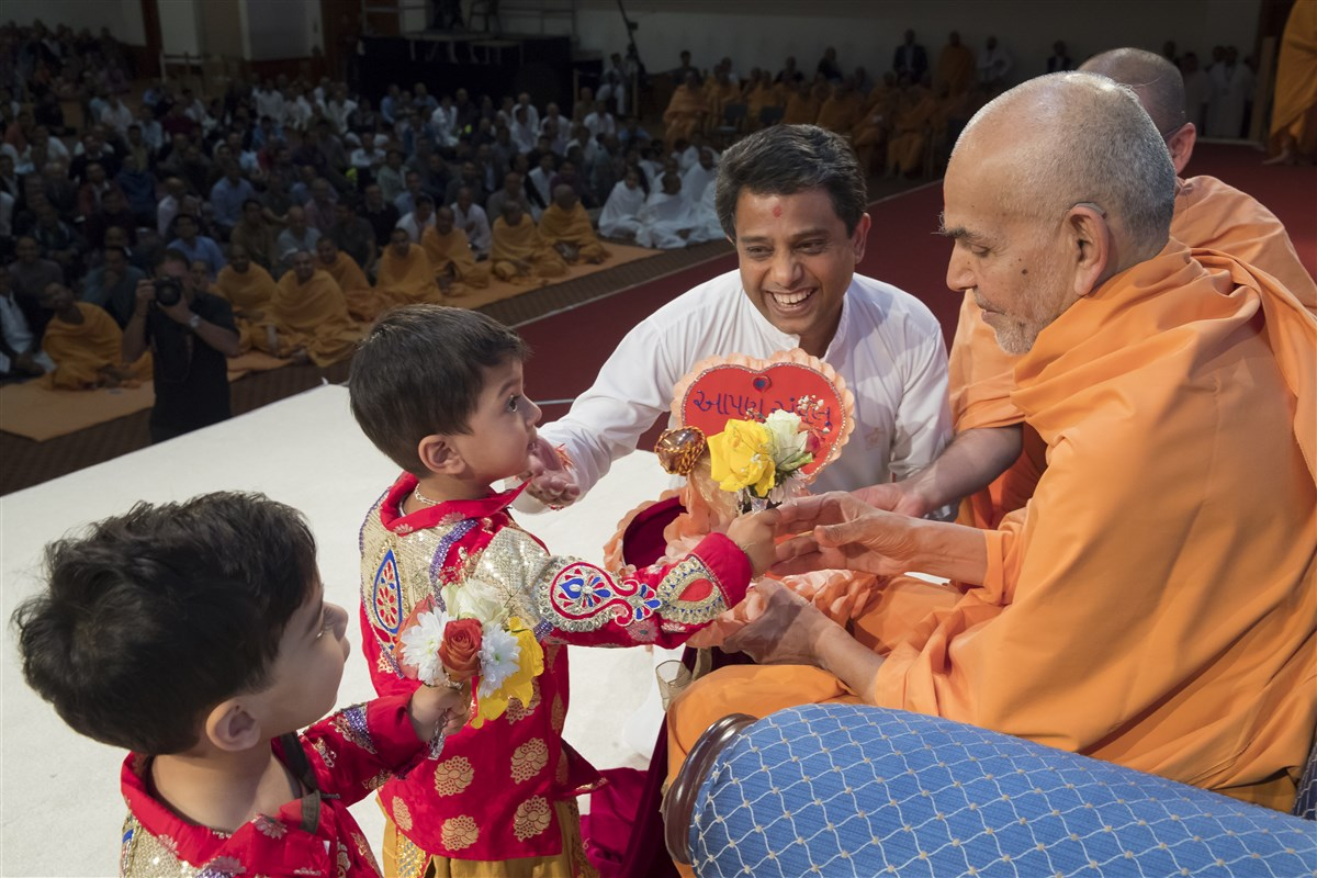 Children and a senior volunteer present Swamishri with flowers and a decorative invitation
