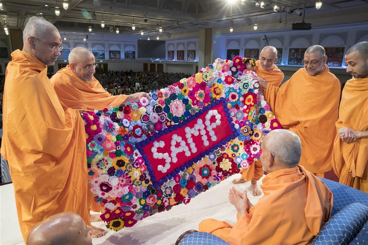 Swamis present a decorative shawl to Swamishri