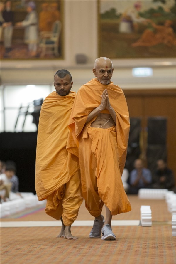 Swamishri greets devotees with folded hands during his walk