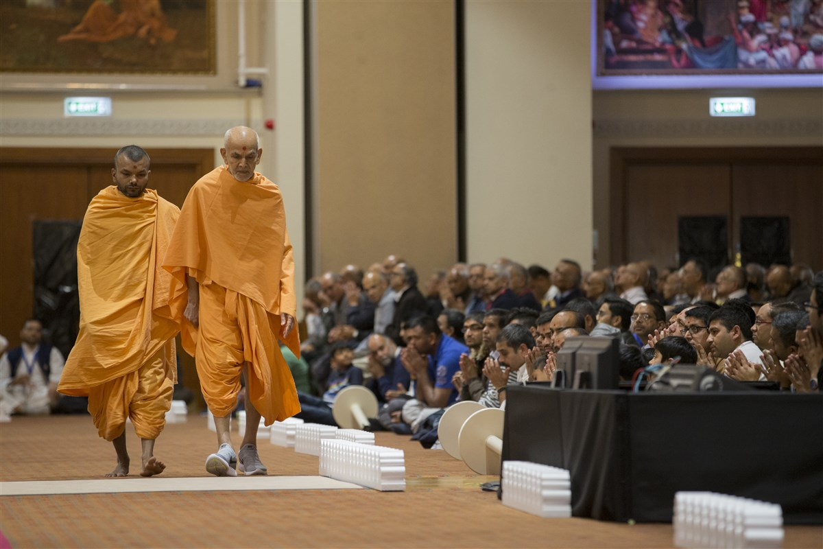 Swamishri walking in the assembly hall