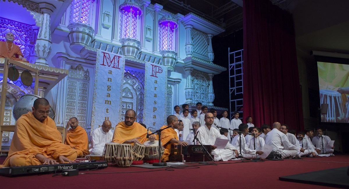 Swamis and devotees of all ages perform the 'Samp Geet'