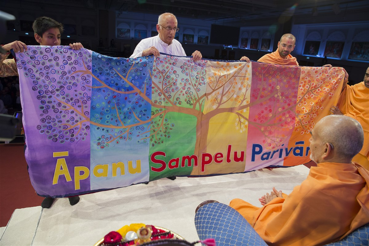 Swamis and volunteers present a decorative shawl to Swamishri representing the united family tree of BAPS