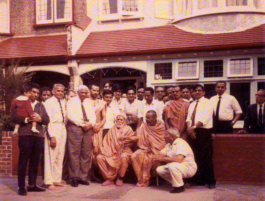 Yogiji Maharaj with Pramukh Swami, Mahant Swami and devotees outside the same house, in 1970