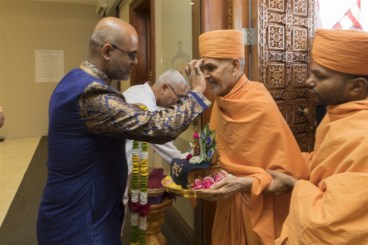 A lead volunteer welcomes Harikrishna Maharaj and Swamishri with a traditional pujan and garland