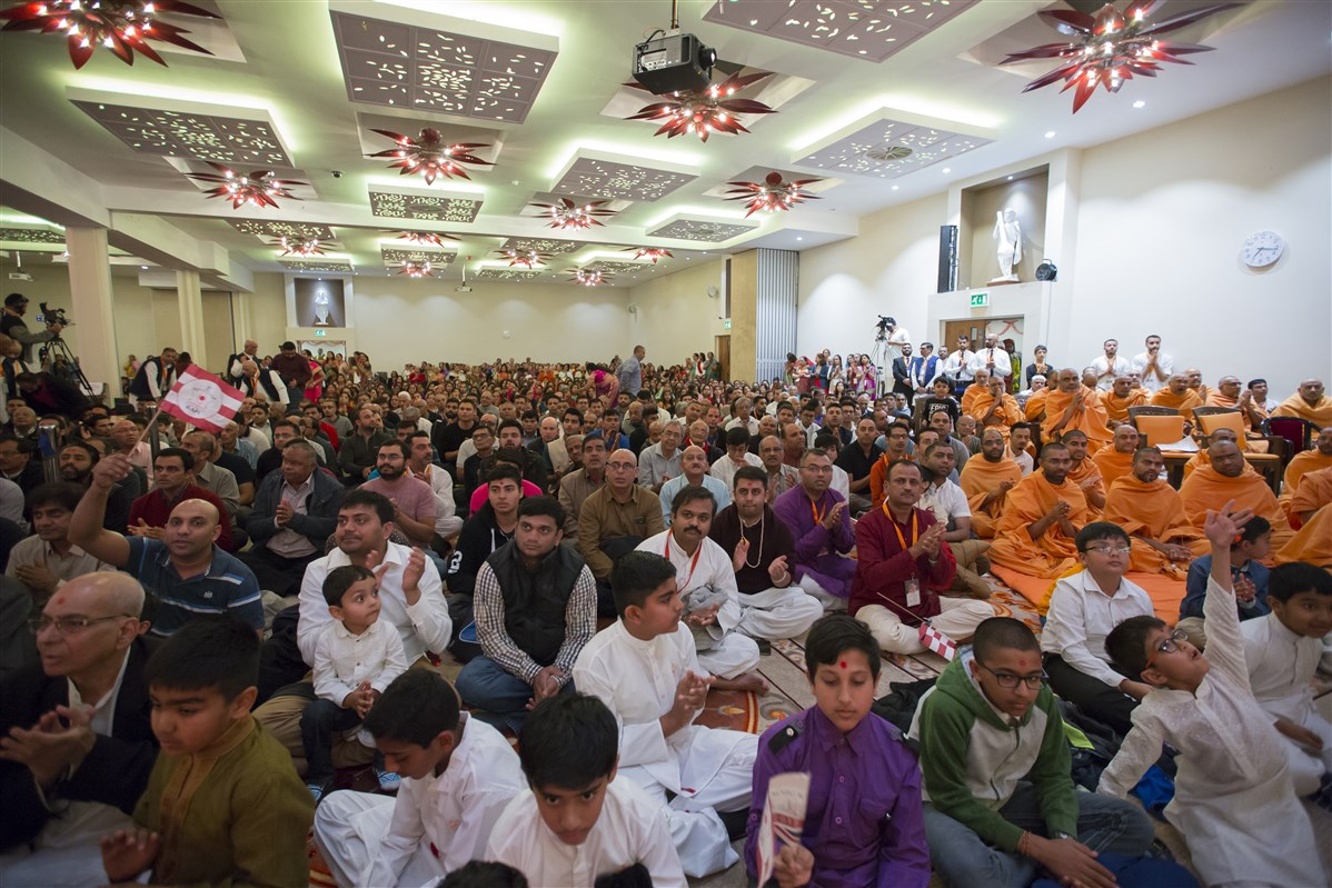 Hundreds of devotees warmly welcome Swamishri to the assembly