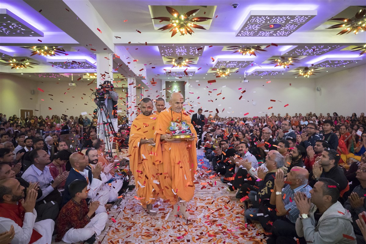 Swamishri arrives in the evening assembly with Harikrishna Maharaj to a rapturous devotional welcome