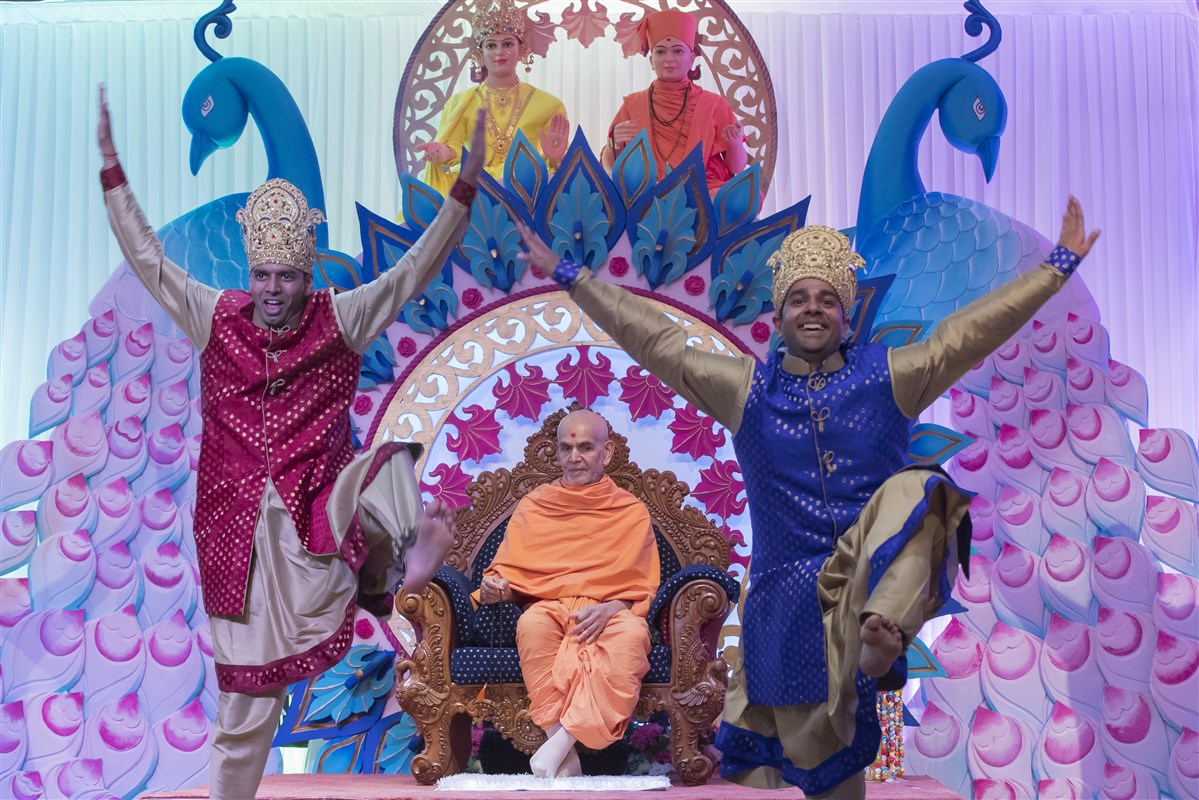 Youths perform a vibrant dance to welcome Swamishri