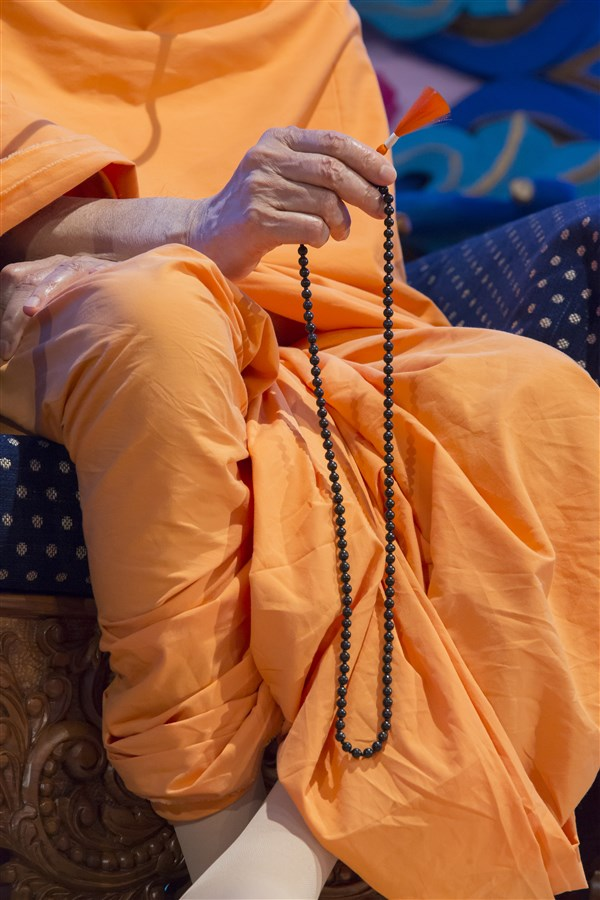 Swamishri continues chanting the mala throughout the grand welcome