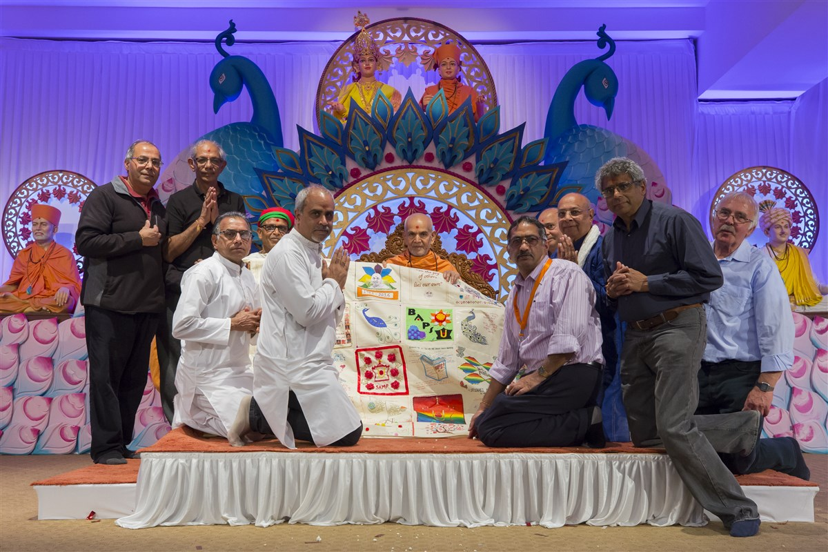 Service volunteers from around the country honour Swamishri with a decorative shawl