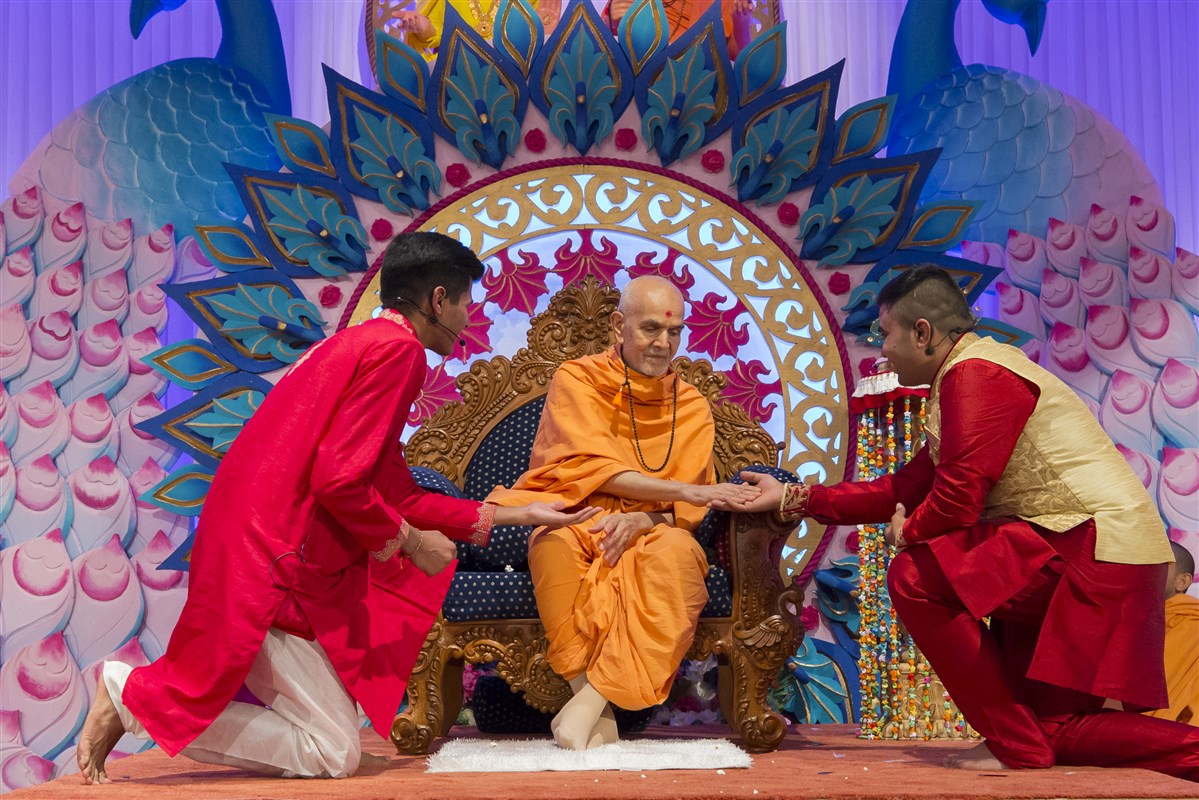 Swamishri engages with the two presenters