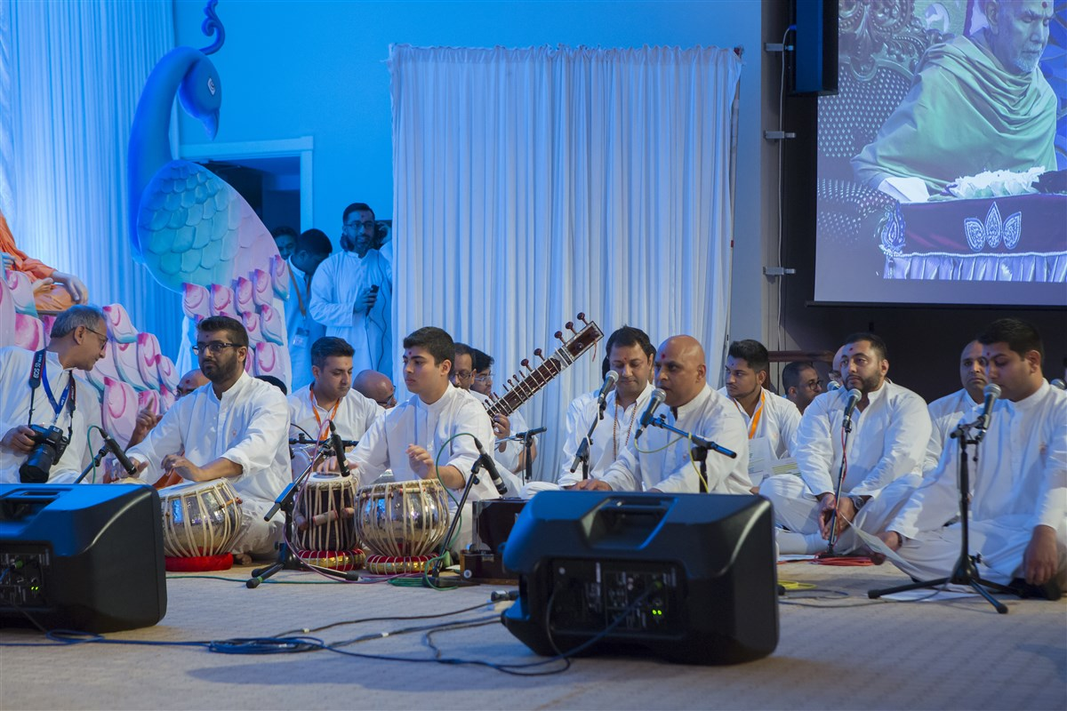 Devotees sing in Swamishri's puja to the accompaniment of musical instruments