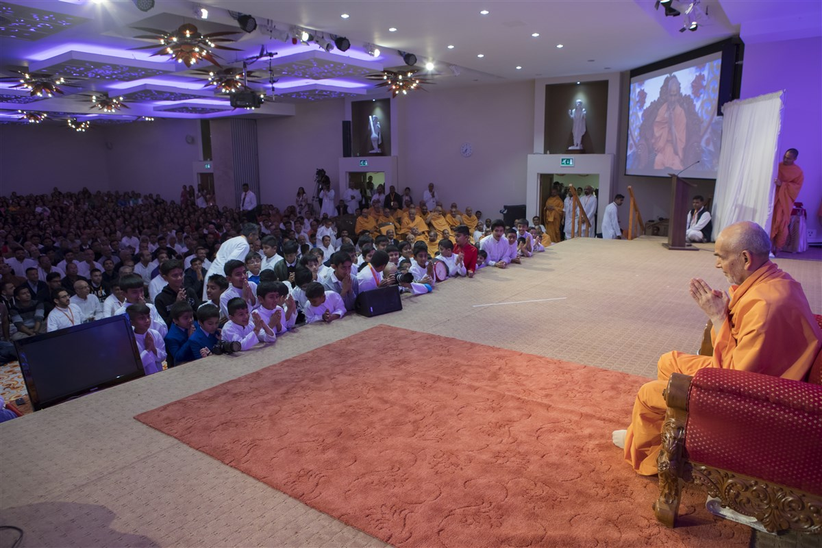 Children enthusiastically greet Swamishri with folded hands