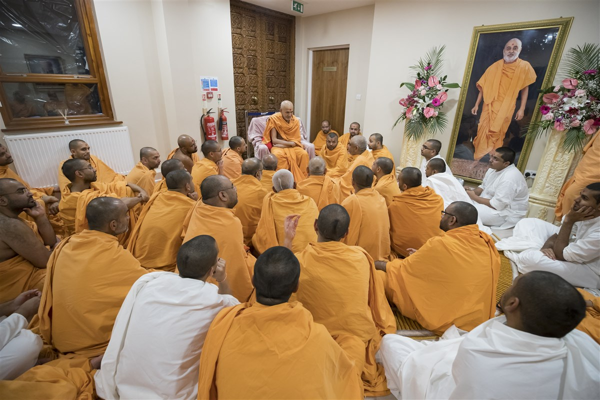 Swamishri engages in a spiritual discussion with the swamis