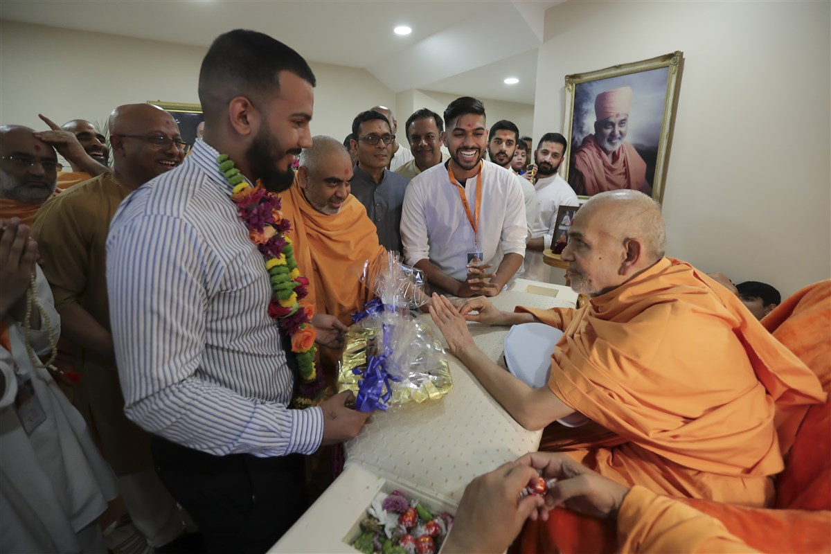Swamishri blesses a youth and his family