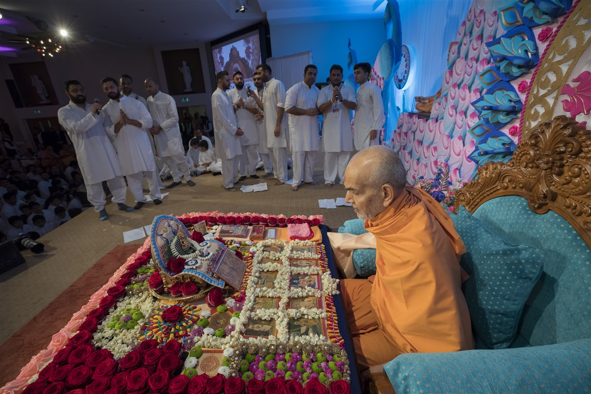 Youths from around the UK offer a collective prayer before Swamishri in his puja