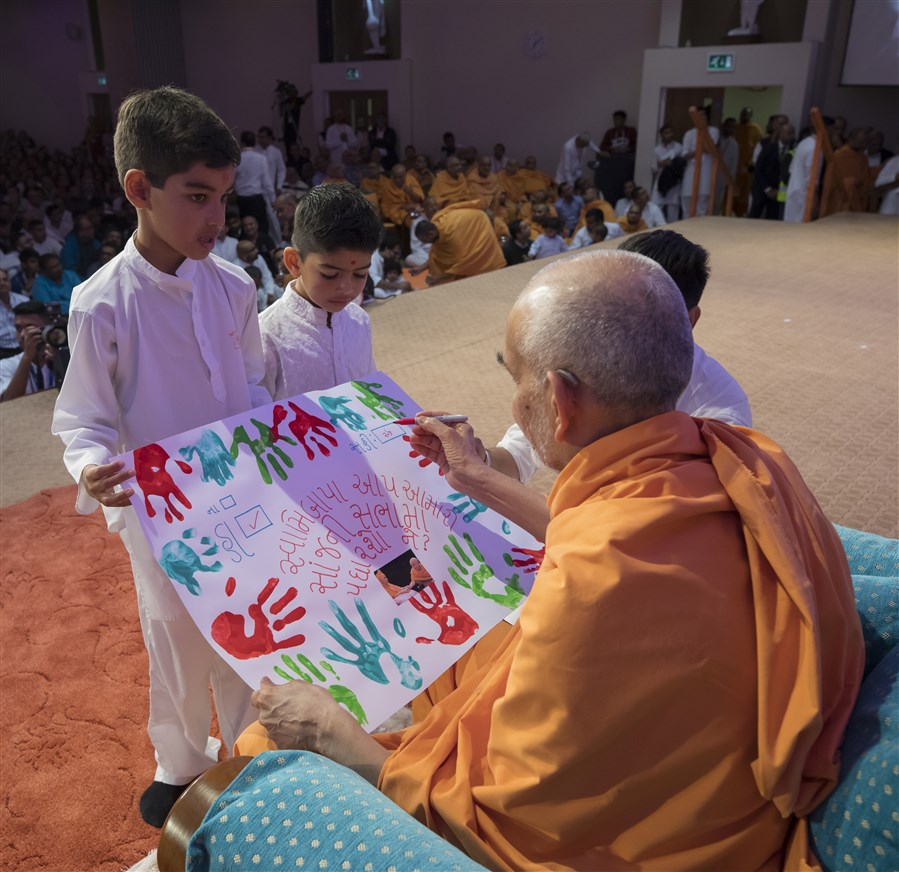 Children invite Swamishri to the evening assembly
