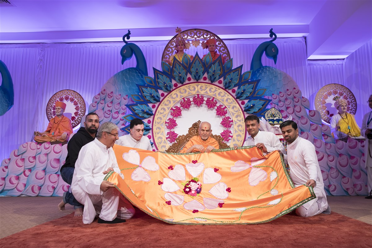 Volunteers honour Swamishri with a decorative shawl