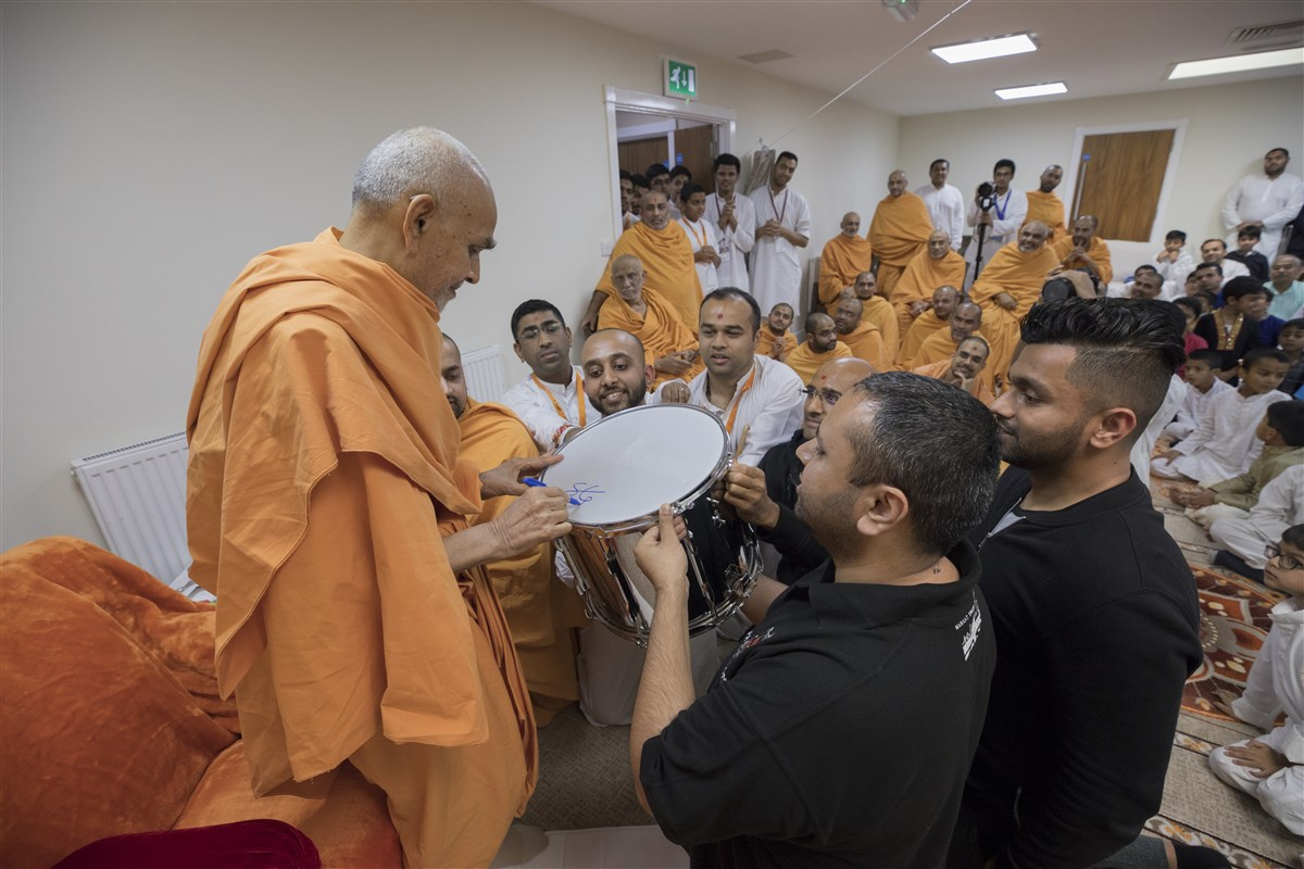 Swamishri blesses the drum with his initials