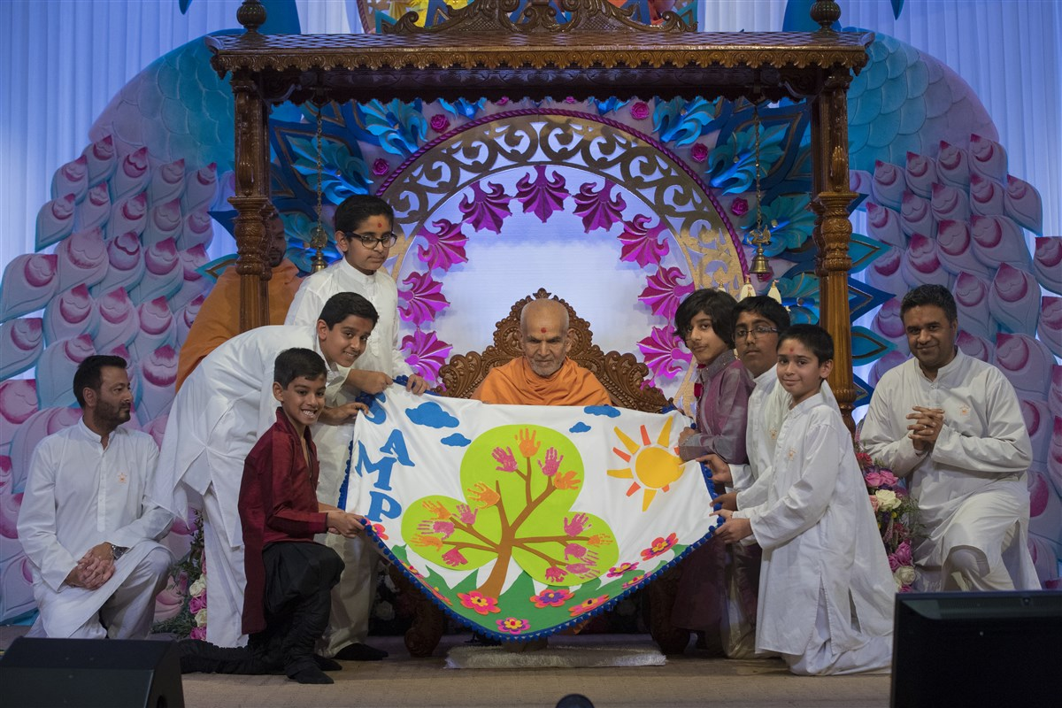 Children honour Swamishri with a decorative shawl